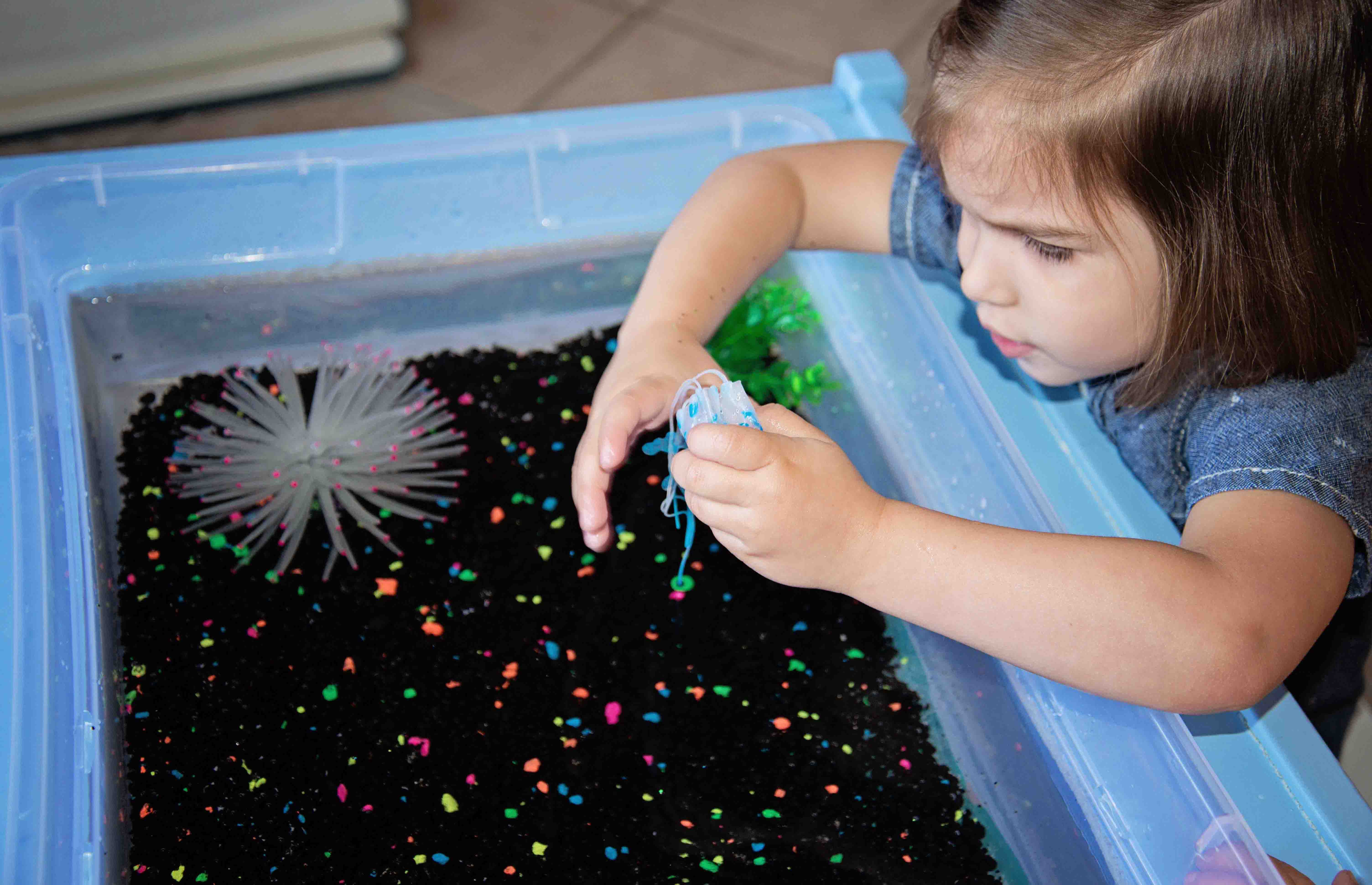 A glowing ocean sensory bin with a realistic anemone, jellyfish and swimming clownfish from Babes in Deutschland