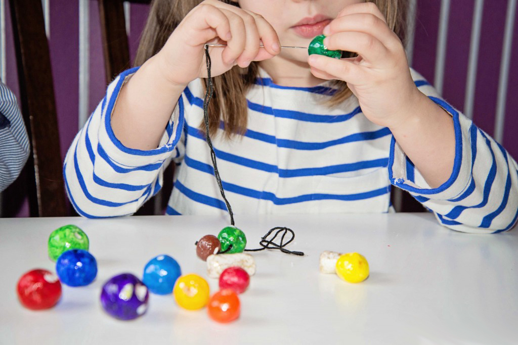 DIY Clay Beads using baking soda and cornstarch, then paint and string! Learn about the color spectrum and different color gradients with this activity from Life Lesson Plans