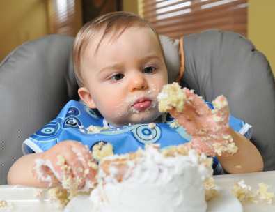 baby boy celebrating his first birthday with cake